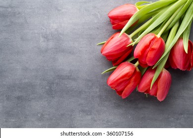 Red tulips on a wooden background.
