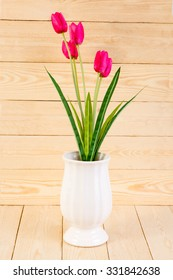 Red tulips in pot on wood texture background