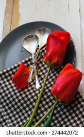 Red tulips with table set on a napkins, rustic