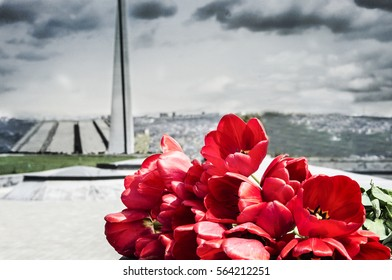 Red tulips in Tsitsernakaberd with Armenian genocide memorial on background. Copy space