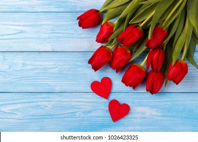 Red tulips and two wooden hearts over blue wooden background, overhead view with copy space