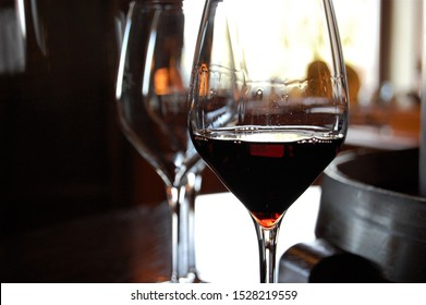 Red Tuscany Italian wine in a glass in foreground and another glass and blurred interior background