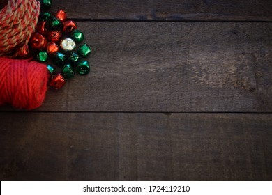 Red twine and red, green, and gold bells on worn, weathered brown wood.