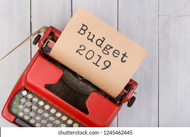 "Red typewriter with the text ""Budget 2019"" on white wooden background"