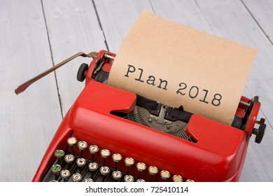 "Red typewriter with the text ""Plan 2018"" on white wooden background"