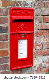 Red UK post box in a brick wall