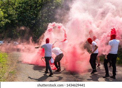 red ultras fans with torches and smokes make an ambush on the street. hooligans with red head masks close the road.