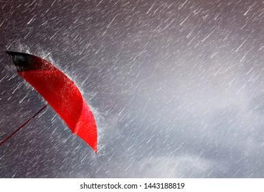 Parapluie rouge sur la tempête, arrière-plan ciel et groupe de nuages noirs et pluie, prévention des risques de pluie et de vent, sauvegarde de la planification et des soins de santé, orage avec concept d'assurance, protection contre les accidents