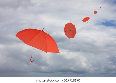 Red umbrella blown by wind,concept for management business idea on rain cloud background.