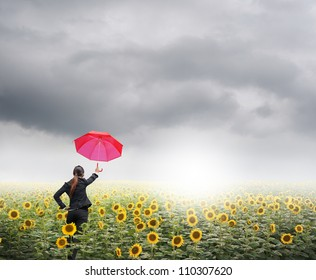 Red umbrella Business woman standing in rainclouds over sunflowers field