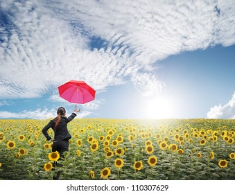 Red umbrella Business woman standing in blue sky over sunflowers field