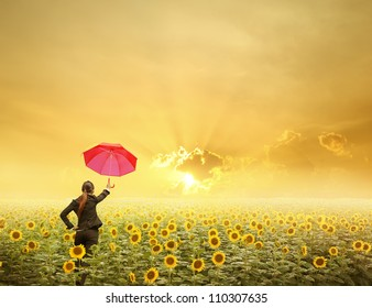 Red umbrella Business woman standing in sunset over sunflowers field