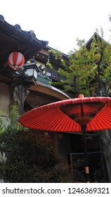 red umbrella in front of Japanese ryokan style hotel entrance