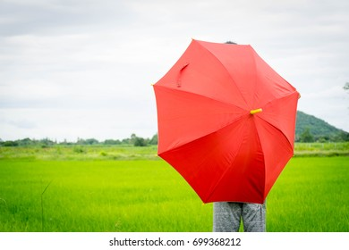 Red umbrella girl playing on green field for background usage ,dramatic concept
