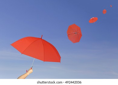 Red umbrella in hand on blue sky background,umbrella blown by the wind in concept for management business idea.