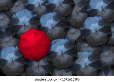 A red umbrella stands out against a crowd of black ones. Individuality and leadership concept.
