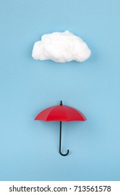 red umbrella under the cloud on sky blue background