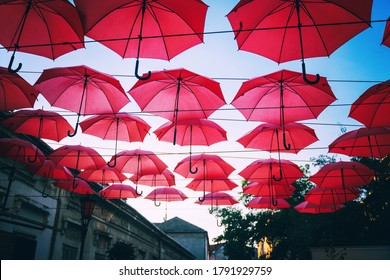 Red umbrellas over street in european city, urban festive background and texture