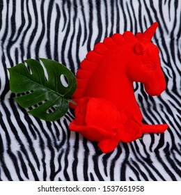 Red unicorn souvenir on zebra background. Minimal art