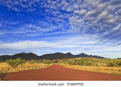 red unsealed road towards national park Flinders Ranges - its Welpena pound mountain range. Warm sun light at sunrise with blue cloudy sky.