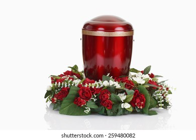 Red urn and floral wreath on white background