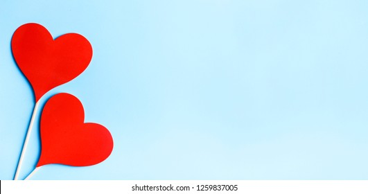 Red valentine hearts on pastel blue background from above. Valentine's day celebration banner. Creative minimal love concept. Hearts balloons top view. Valentine pop art colorful simple design layout.