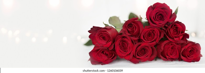 Red valentines roses on white vintage background with tender bokeh