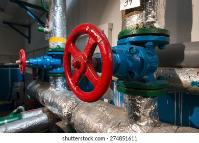 Red valve located on the flange of the blue pipe in the boiler room
