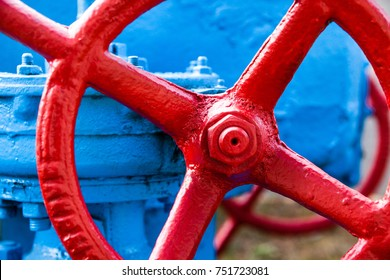 Red valve on the blue pipe. Valve with wheel handle. Industrial gear. Close-up.