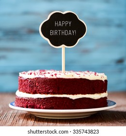 a red velvet cake with a chalkboard in the shape of a thought bubble with the text happy birthday, on a rustic wooden table