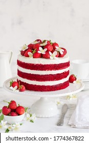 Red velvet cake decorated with strawberries and jasmine flowers on a white stand. Selective focus