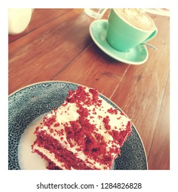 red velvet cake on blue plate and large frothy capuccino