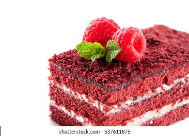Red Velvet cake piece close-up isolated on white background with raspberries and mint leaves on top