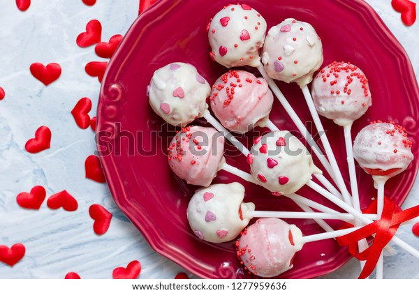 Red velvet cake pops covered in white chocolate decorated with red and pink sugar sprinkles, sweet treats for valentine day