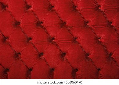 Red velvet capitone textile background, retro Chesterfield style checkered soft tufted fabric furniture diamond pattern decoration with buttons, close up