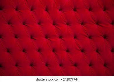 Red velvet couch background texture with sunken buttons.
