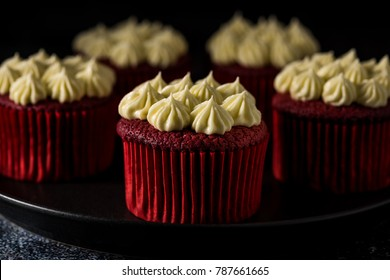 Red Velvet cup cakes on plates and a cake stand