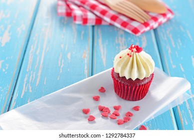 Red velvet cupcake with cream cheese frosting decorated with mini heart on blue wooden table for Valentine's Day with copy space.Homemade Bakery for Designed work. Concept about love and relationship.