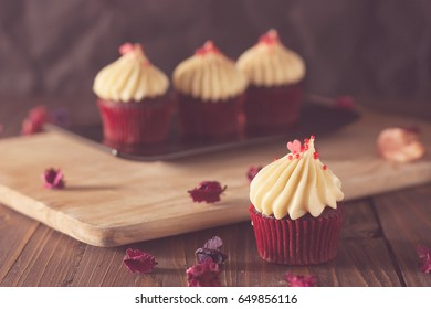 red velvet cupcakes with cream cheese icing decorate with dry flowers on wood board in soft tone