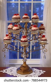 Red velvet cupcakes displayed on a chandelier in front of a window