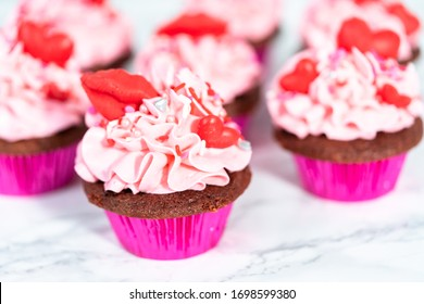 Red velvet cupcakes with pink Italian buttercream frosting and decorates with heart and kiss shaped red chocolates.