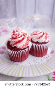 Red velvet cupcakes with white icing and red sugar sit on a pretty plate.  A nice Valentine's Day theme with silver and red hearts and a sparkly background.