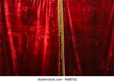 Red velvet curtain with gold fringe.