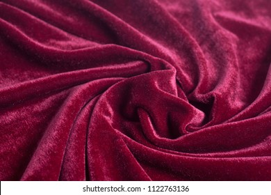 Red velvet fabric with spiral folds closeup