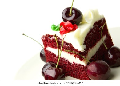 Red velvet layer cake with white frosting garnished with fresh cherries against white background.