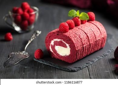 Red velvet Sponge Swiss roll with fresh raspberry on dark background