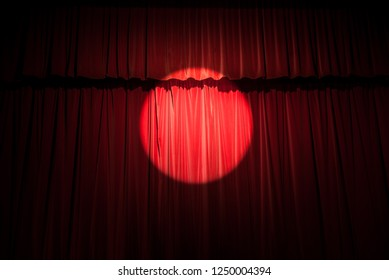 Red velvet stage curtain with spotlight background.