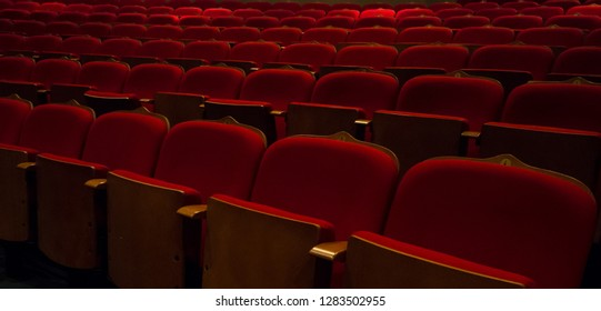 Red velvet theater seats. Empty cinema line seats with numbers on it.