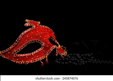 Red Venice mask and black pearls with reflection over black background