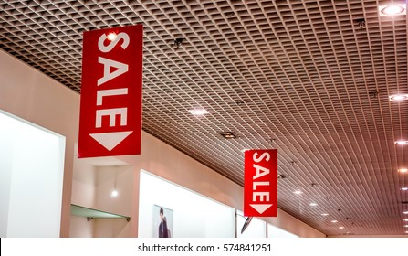red vertical sale posters with white letters hang from grid ceiling in big shop in sale season. sale poster board at fashion clothes shopfront
